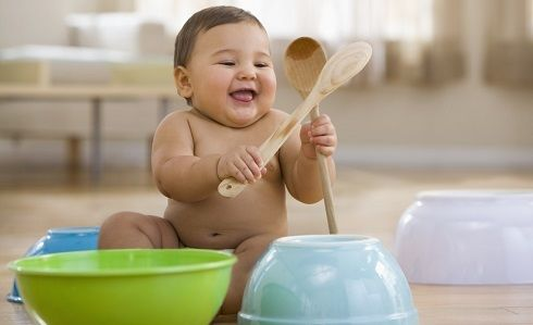 baby playing with spoons and bowls