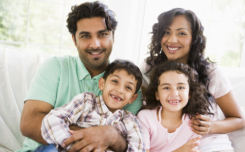 latino family smiling on couch