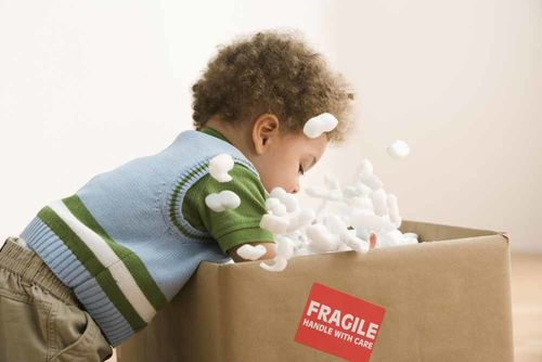 toddler playing with a box
