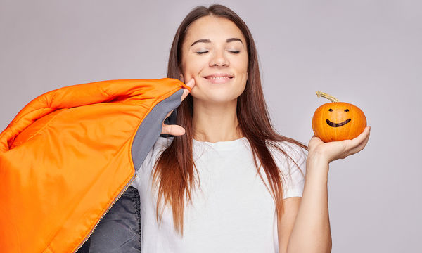 Woman holding small pumkin and smiling